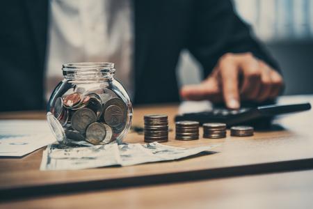 Sluit omhoog van de bedrijfsmens die met muntstukken en geld aan de lijst in zijn bureau in financiën, investering, besparing en bankwezen werken Stockfoto