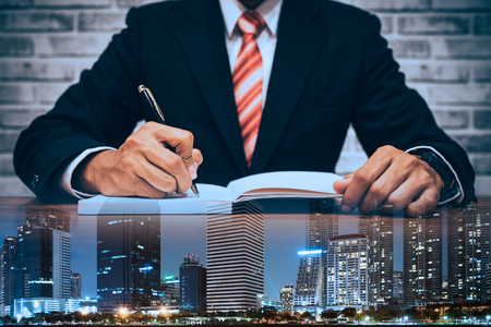 organise: double exposure of Businessman in suit writing or signing in notebook on wooden table with city  in business concept