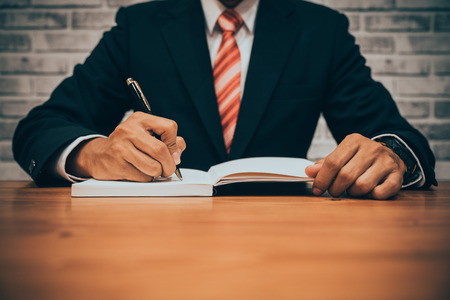 organise: Businessman in suit writing or signing in notebook on wooden table in business concept Stock Photo