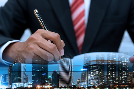 organise: double exposure of Businessman in suit writing or signing in notebook on wooden table and the city in business concept Stock Photo