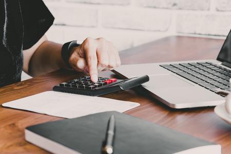 Femmes d'affaires travaillent avec calculatrice et ordinateur portable, stylo et bloc-notes sur la table en bois Banque d'images - 77249613