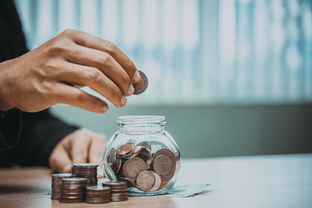 Close up of business man hand putting the coins on the table in his office in finance,investment,saving and banking conept