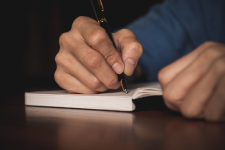 organise: Close up of  people hand  writing on notebook on wooden table