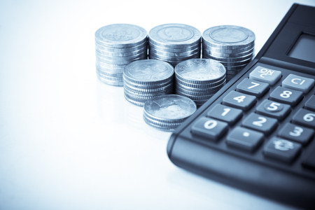 Row of coins and calculator on the wooden tablein finance and banking concept