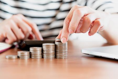 commodities: Primer plano de la mano de la mano de la mano de la calculadora y el dinero, las monedas en la banca financiera y el concepto de ahorro