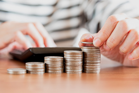 Close up of people hand work calculator and money,coins in finance banking and saving concept