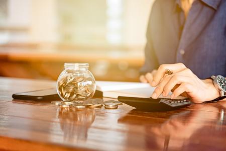 Sluit omhoog van het werkcalculator van de mensenhand en geld, muntstukken in financiënbankwezen en besparingsconcept Stockfoto