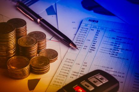 Reihe der Münzen, der Autofernbedienung und des Stiftes auf Konto buchen im Autofinanz- und -bankwesenkonzept Standard-Bild - 77250828