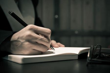 Close up de la gente de negocios mano en traje de escribir en un cuaderno o un documento Foto de archivo