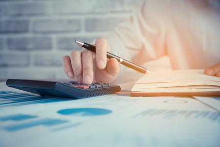 Femmes d'affaires travaillent avec calculatrice et ordinateur portable, stylo et bloc-notes sur la table en bois Banque d'images - 77251018