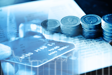 Double exposure of rows of coins onthe book bank and the close up of people hand insert card to ATM in finance and banking concept Stock Photo
