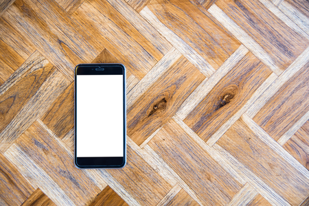 Mobile phone with the blank white screen on the wooden texture table