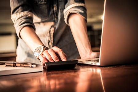 Femmes d'affaires travaillent avec calculatrice et ordinateur portable, stylo et bloc-notes sur la table en bois