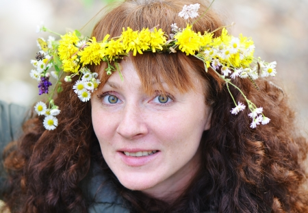 Close-up of a young curly woman with freckles wearing a wreath of wildflowers photo