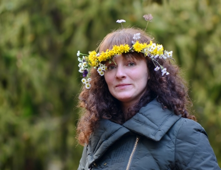 face in tree bark: Portrait of a young woman wearing a wreath of wild flowers in nature