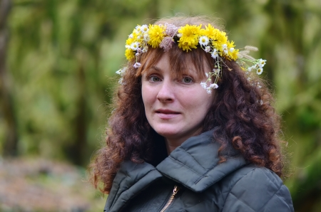 Young woman wearing a wreath of wild flowers in nature photo