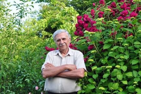 Vecchio giardiniere maschio nel giardino primavera sta con le braccia conserte