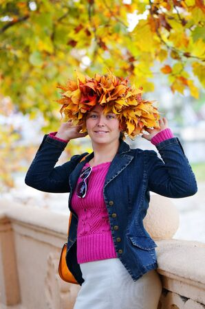 Beautiful yound woman in a wreath of colorful autumn leaves photo