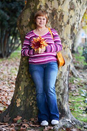 Ritratto di una donna adulta nel parco autunno con un mazzo di foglie colorate