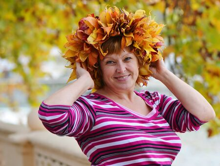 Portrait of a happy mature woman in a wreath of bright autumn leaves photo