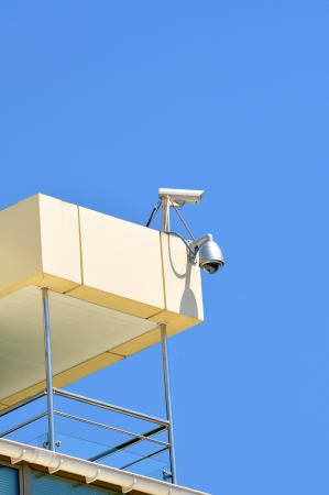 sky bachground: Two cameras outdoor video surveillance on the roof of an morden building on a sunny cloudless day Stock Photo