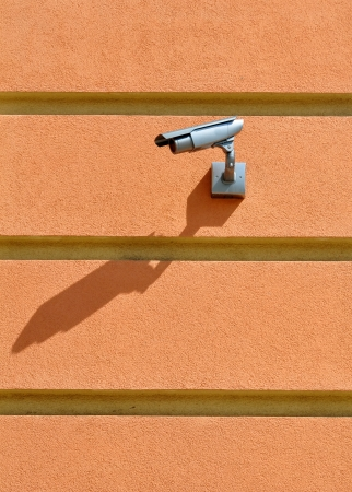 CCTV camera surveillance on the striped pink stucco wall watch left photo