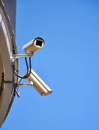 Two CCTV security cameras and blue sky photo