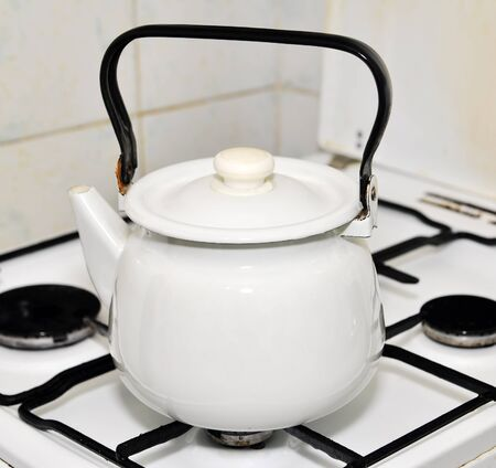 White metal kettle on a gas stove in a kitchen photo
