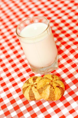 Breakfast  glass of milk and two shortbread on tablecloth