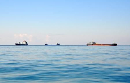 Three cargo ships on horizon Stock Photo - 17400930