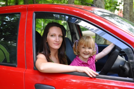 Mother and daughter sitting in a red car photo