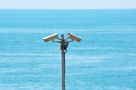 Two surveillance cameras in opposite directions against the sea photo