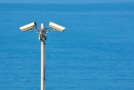 Two CCTV surveillance cameras on the sea background  the right place for text  photo