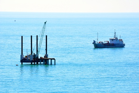 suction: Port crane and suction hopper dredger working on  a building of a new pier in sea port of Sochi, Russia