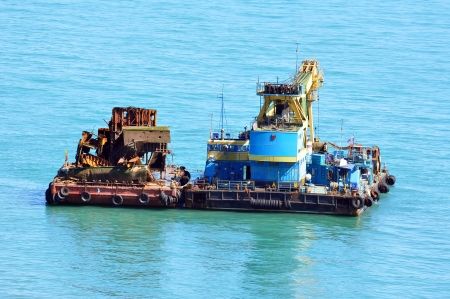 Floating crane transports the platform with the scrap metal photo