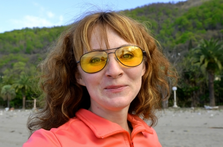 Funny portrait of a red-haired young woman in yellow sunglasses in nature photo