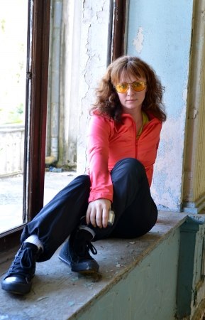 Young red-haired woman in yellow sunglasses sitting on the windowsill of the destroyed building photo