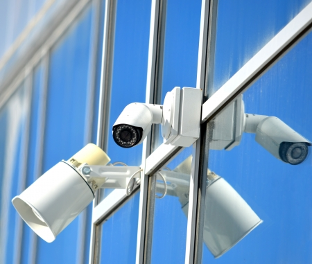 CCTV camera and loudspeaker on a glass facade outdoors photo