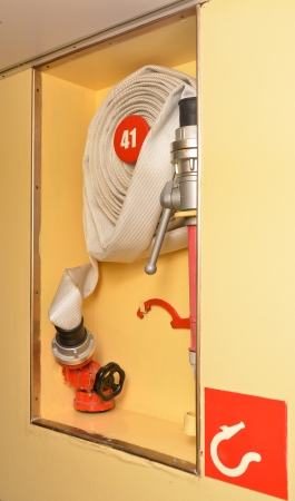 Rolled up light canvas firehose in a niche on a cruise ship is attached to a hydrant and ready for use in fire alarm Stock Photo - 25449660