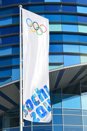 SOCHI, RUSSIA - FEBRUARY 7, 2014: Olympic flag with the symbol of the Sochi 2014 in front of the Ice rink for figure skating �Iceberg� in Olympic park  Editorial