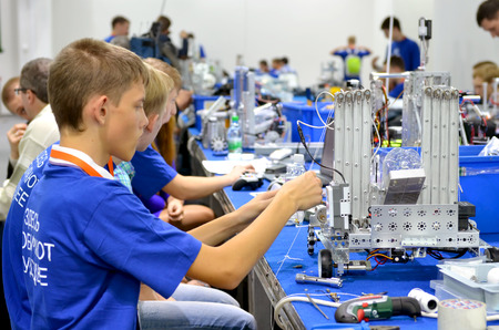 attended: SOCHI, RUSSIA – November 21, 2014: Children make a robot at the robot Olympiad in Sochi . Here there was the World Robotic Olympiad 2014. It was attended by delegates from 47 countries. Editorial