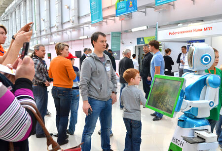delegates: SOCHI, RUSSIA � November 21, 2014: People comminicate whith android robot in Sochi. Here there was the World Robotic Olympiad 2014. It was attended by delegates from 47 countries.