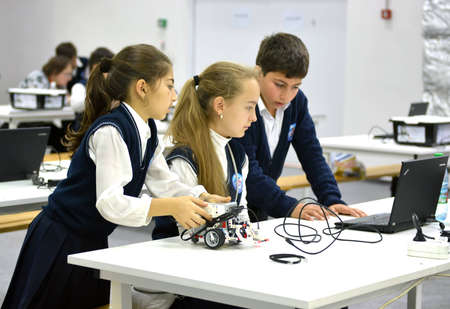 SOCHI, RUSSIA – November 21, 2014: Children make a robot at the World Robotic Olympiad Russia 2014. It was attended by delegates from 47 countries.