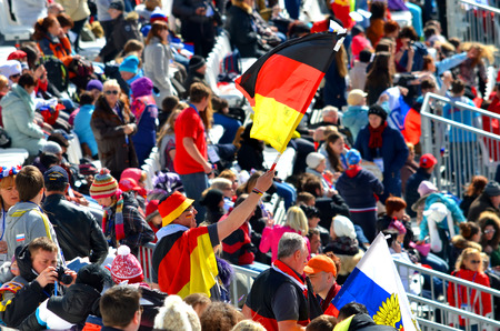 SOCHI, RUSSIA - March 16, 2014: Sport fun man with national flag of Germany on Winter Paralympic Games  in Sochi. Giant Slalom, final day.