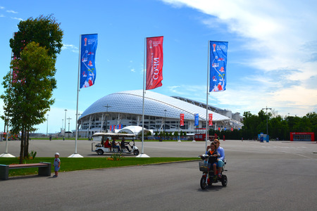 SOCHI, RUSSIA � June 16, 2017: A tourist electric car and a family on an electric bike in the background of the Fisht stadium in the Olympic Park in Sochi