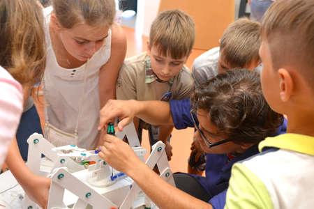 SOCHI, RUSSIA - June 24, 2017: Teacher helps schoolchildren to design a robot in an open lesson on robotics of the All-Russian Educational Center