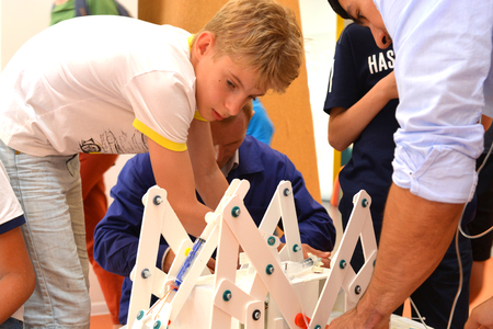 SOCHI, RUSSIA - June 24, 2017: A schoolboy with a teacher completes the construction of a robot in an open lesson of the All-Russian Educational Center