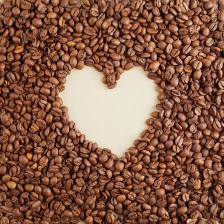 A heart symbol made from coffee crops on hand-made paper photo