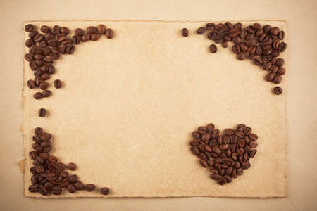 A frame and a heart symbol made from coffee crops on hand-made paper, plenty of place for text photo