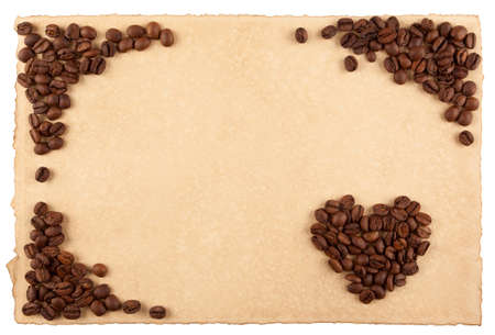 A frame and a heart symbol made from coffee crops on hand-made paper and isolated on white  Place for text  photo